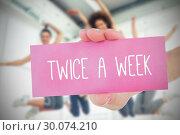 Купить «Woman holding pink card saying twice a week», фото № 30074210, снято 21 марта 2014 г. (c) Wavebreak Media / Фотобанк Лори