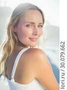 Pretty blonde standing at the beach in white sundress . Стоковое фото, агентство Wavebreak Media / Фотобанк Лори