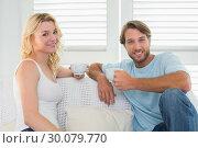 Купить «Smiling casual couple sitting on couch having coffee», фото № 30079770, снято 24 января 2014 г. (c) Wavebreak Media / Фотобанк Лори