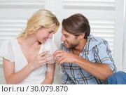 Купить «Cute young couple sitting on floor together having white wine», фото № 30079870, снято 24 января 2014 г. (c) Wavebreak Media / Фотобанк Лори