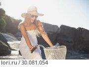 Beautiful smiling blonde in sundress on bike at the beach. Стоковое фото, агентство Wavebreak Media / Фотобанк Лори