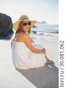 Beautiful smiling blonde in sundress sitting on the beach. Стоковое фото, агентство Wavebreak Media / Фотобанк Лори