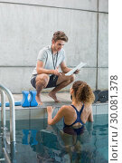 Купить «Swimmer talking to her coach poolside», фото № 30081378, снято 26 февраля 2014 г. (c) Wavebreak Media / Фотобанк Лори