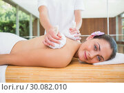 Купить «Smiling woman getting a back massage with herbal compresses», фото № 30082010, снято 9 апреля 2014 г. (c) Wavebreak Media / Фотобанк Лори
