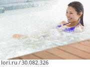 Купить «Smiling brunette in bikini relaxing in hot tub», фото № 30082326, снято 8 апреля 2014 г. (c) Wavebreak Media / Фотобанк Лори