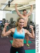 Купить «Happy muscular man and woman lifting weights », фото № 30082578, снято 2 апреля 2014 г. (c) Wavebreak Media / Фотобанк Лори