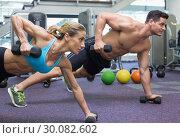Купить «Bodybuilding man and woman holding dumbbells in plank position», фото № 30082602, снято 2 апреля 2014 г. (c) Wavebreak Media / Фотобанк Лори