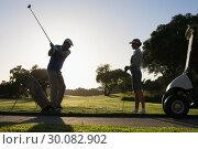 Купить «Golfing couple teeing off for the day», фото № 30082902, снято 3 апреля 2014 г. (c) Wavebreak Media / Фотобанк Лори