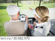 Купить «Golfing couple driving in their golf buggy with woman pointing», фото № 30082970, снято 3 апреля 2014 г. (c) Wavebreak Media / Фотобанк Лори