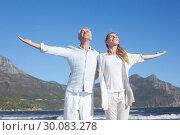 Купить «Happy couple standing with arms outstretched at the beach», фото № 30083278, снято 3 апреля 2014 г. (c) Wavebreak Media / Фотобанк Лори