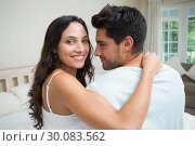 Attractive couple sitting on bed. Стоковое фото, агентство Wavebreak Media / Фотобанк Лори