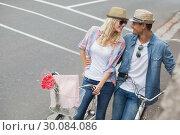 Купить «Hip young couple going for a bike ride», фото № 30084086, снято 19 февраля 2014 г. (c) Wavebreak Media / Фотобанк Лори