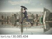 Купить «Composite image of businessman jumping on tightrope holding an umbrella», фото № 30085434, снято 11 июня 2014 г. (c) Wavebreak Media / Фотобанк Лори
