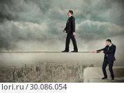Купить «Young business man pulling a tightrope for businessman», фото № 30086054, снято 11 июня 2014 г. (c) Wavebreak Media / Фотобанк Лори