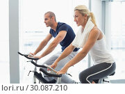 Купить «Determined couple working on exercise bikes at gym», фото № 30087210, снято 27 февраля 2014 г. (c) Wavebreak Media / Фотобанк Лори