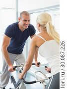 Купить «Smiling couple working on exercise bikes at gym», фото № 30087226, снято 27 февраля 2014 г. (c) Wavebreak Media / Фотобанк Лори