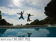 Купить «Couple jumping into swimming pool», фото № 30087702, снято 8 апреля 2014 г. (c) Wavebreak Media / Фотобанк Лори