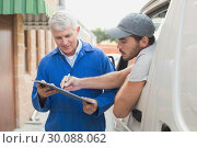 Delivery driver showing customer where to sign. Стоковое фото, агентство Wavebreak Media / Фотобанк Лори