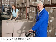 Купить «Warehouse foreman smiling at camera with trolley», фото № 30088074, снято 10 мая 2014 г. (c) Wavebreak Media / Фотобанк Лори