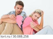 Купить «Young couple holding two halves of broken heart», фото № 30088258, снято 29 апреля 2014 г. (c) Wavebreak Media / Фотобанк Лори