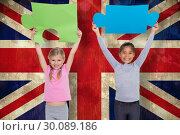 Composite image of elementary pupils holding jigsaw pieces. Стоковое фото, агентство Wavebreak Media / Фотобанк Лори