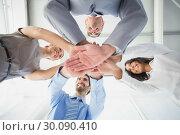 Купить «Four workers stacking hands together», фото № 30090410, снято 6 мая 2014 г. (c) Wavebreak Media / Фотобанк Лори