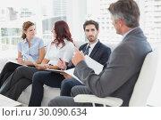 Купить «Business team discussing work notes», фото № 30090634, снято 6 мая 2014 г. (c) Wavebreak Media / Фотобанк Лори