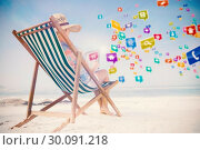 Купить «Composite image of woman in sunhat sitting on beach in deck chair using tablet pc», фото № 30091218, снято 22 августа 2014 г. (c) Wavebreak Media / Фотобанк Лори