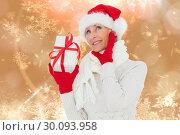 Купить «Composite image of festive woman holding gift», фото № 30093958, снято 26 августа 2014 г. (c) Wavebreak Media / Фотобанк Лори