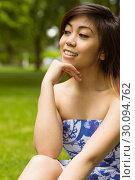 Купить «Beautiful woman with hand on chin in park», фото № 30094762, снято 4 июня 2014 г. (c) Wavebreak Media / Фотобанк Лори