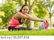 Купить «Happy brunette in sportswear stretching on the grass», фото № 30097818, снято 20 июня 2014 г. (c) Wavebreak Media / Фотобанк Лори