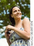 Купить «Portrait of a smiling brunette holding her braid», фото № 30097974, снято 20 июня 2014 г. (c) Wavebreak Media / Фотобанк Лори
