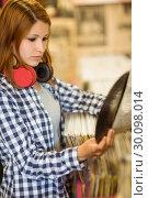 Купить «Redhead with a headphone around the neck holding a vinyl», фото № 30098014, снято 13 июня 2014 г. (c) Wavebreak Media / Фотобанк Лори