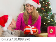 Купить «Sitting couple giving each other presents», фото № 30098970, снято 24 июля 2014 г. (c) Wavebreak Media / Фотобанк Лори