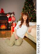 Купить «Pretty redhead sitting on the carpet posing», фото № 30099894, снято 3 октября 2014 г. (c) Wavebreak Media / Фотобанк Лори