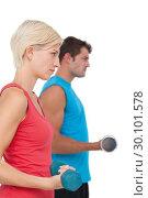 Купить «Fit man and woman lifting dumbbells», фото № 30101578, снято 13 ноября 2014 г. (c) Wavebreak Media / Фотобанк Лори