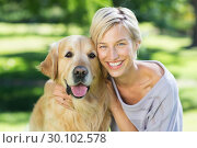Pretty blonde with her dog in the park . Стоковое фото, агентство Wavebreak Media / Фотобанк Лори