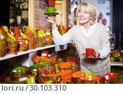 Купить «Smiling mature female holding ceramic cups», фото № 30103310, снято 31 октября 2016 г. (c) Яков Филимонов / Фотобанк Лори
