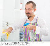 Купить «Young man in apron cleaning shelves», фото № 30103794, снято 20 июня 2019 г. (c) Яков Филимонов / Фотобанк Лори