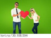 Купить «Composite image of cool young couple holding red heart», фото № 30108594, снято 21 января 2015 г. (c) Wavebreak Media / Фотобанк Лори