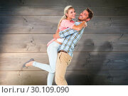 Composite image of handsome man picking up and hugging his girlfriend. Стоковое фото, агентство Wavebreak Media / Фотобанк Лори