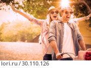 Купить «Hip young couple going for a bike ride», фото № 30110126, снято 19 февраля 2014 г. (c) Wavebreak Media / Фотобанк Лори