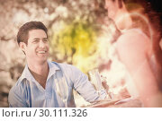 Купить «Couple with champagne flutes sitting at an outdoor café», фото № 30111326, снято 21 ноября 2013 г. (c) Wavebreak Media / Фотобанк Лори