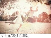 Купить «Cute couple jumping in the park together», фото № 30111382, снято 31 января 2014 г. (c) Wavebreak Media / Фотобанк Лори
