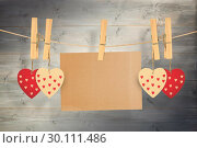 Купить «Composite image of hearts hanging on line with card», фото № 30111486, снято 23 января 2015 г. (c) Wavebreak Media / Фотобанк Лори