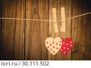 Купить «Composite image of hearts hanging on the line», фото № 30111502, снято 23 января 2015 г. (c) Wavebreak Media / Фотобанк Лори