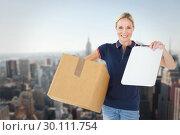 Купить «Composite image of happy delivery woman holding cardboard box and clipboard», фото № 30111754, снято 27 апреля 2015 г. (c) Wavebreak Media / Фотобанк Лори