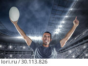 Composite image of portrait of rugby player in blue jersey holding ball with arms raised. Стоковое фото, агентство Wavebreak Media / Фотобанк Лори