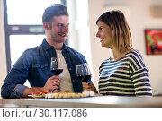 Купить «Couple holding wineglass at counter», фото № 30117086, снято 6 апреля 2016 г. (c) Wavebreak Media / Фотобанк Лори
