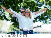 Купить «Couple with arms outstretched standing on street», фото № 30117178, снято 3 февраля 2016 г. (c) Wavebreak Media / Фотобанк Лори